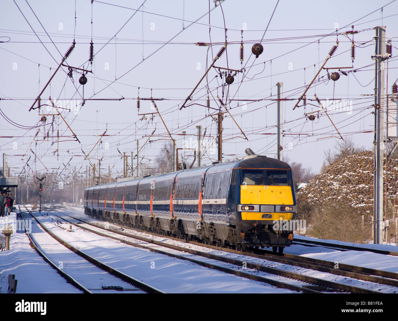 A National Express East Coast electric train passing through a snowy Hitchin. - Stock Image