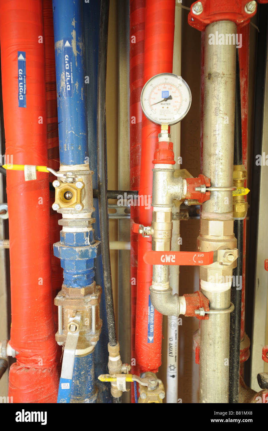 Insulated Water piping red for hot water and blue for cold with water pressure gauge - Stock Image