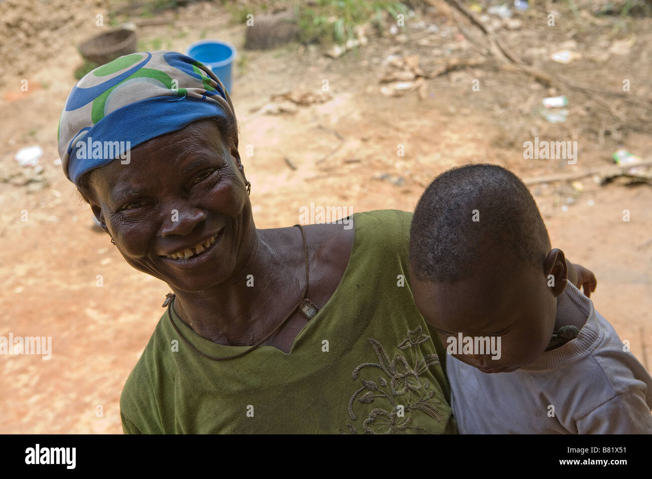 A Nigerian Mother Holding Her Baby Son Poses Outside Of Their