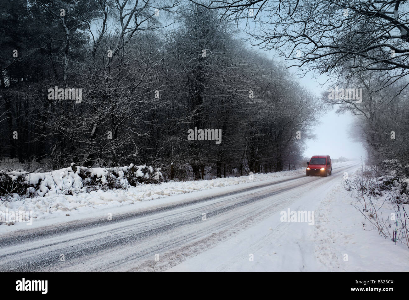 A Post van on a snow covered country lane in North Yorkshire in the United Kingdom - Stock Image