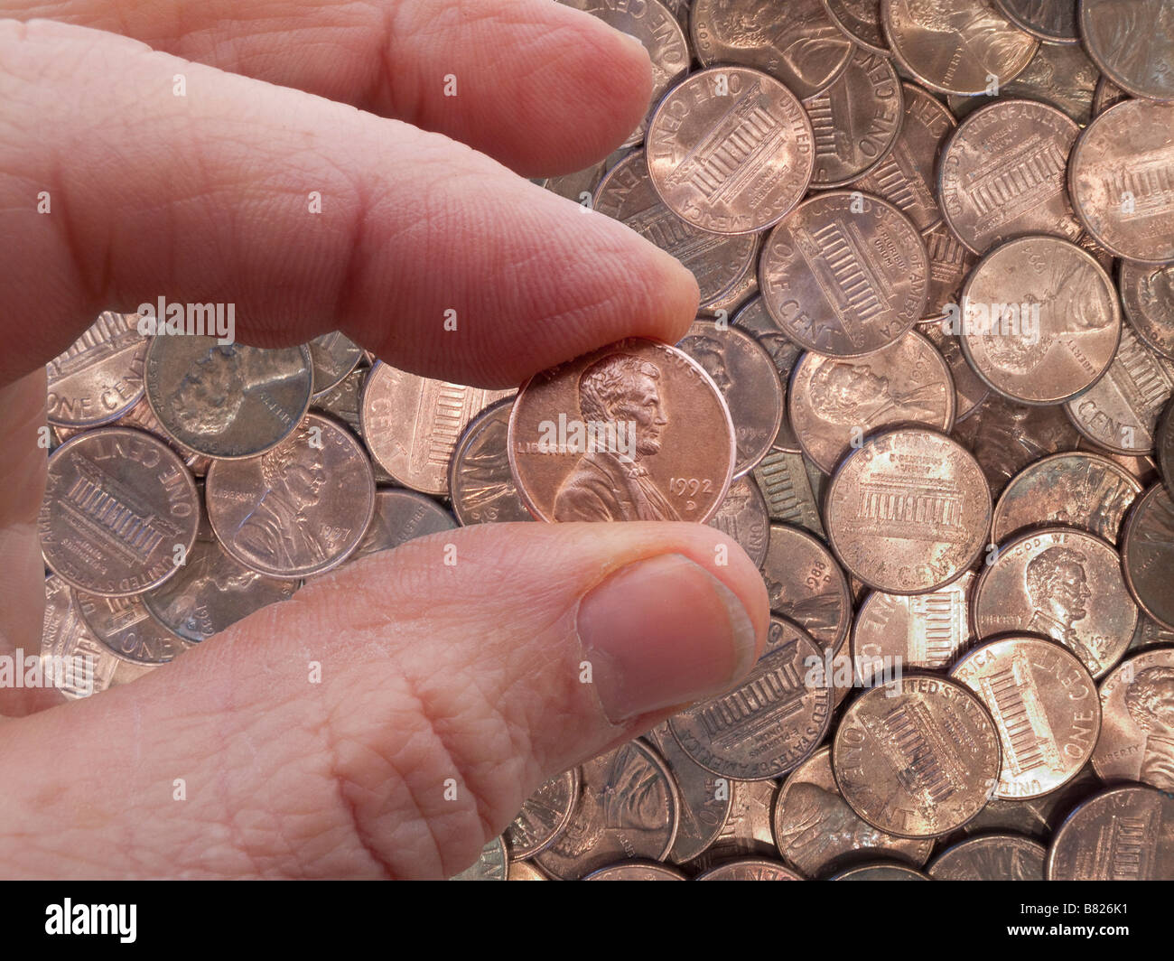 Hand holding penny, pennies as background - Stock Image