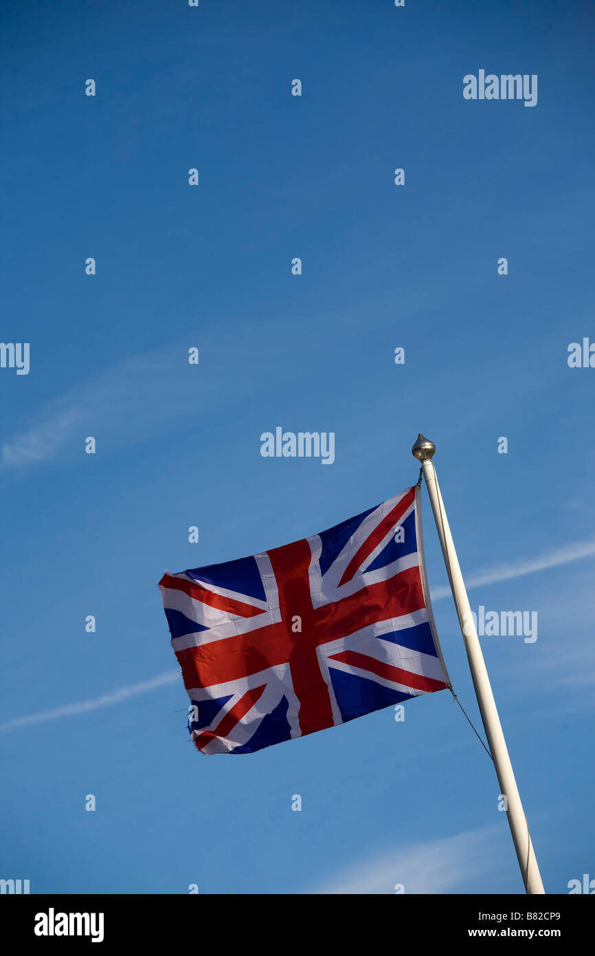 Union Jack flag flying on flagpole against blue sky Stock Photo