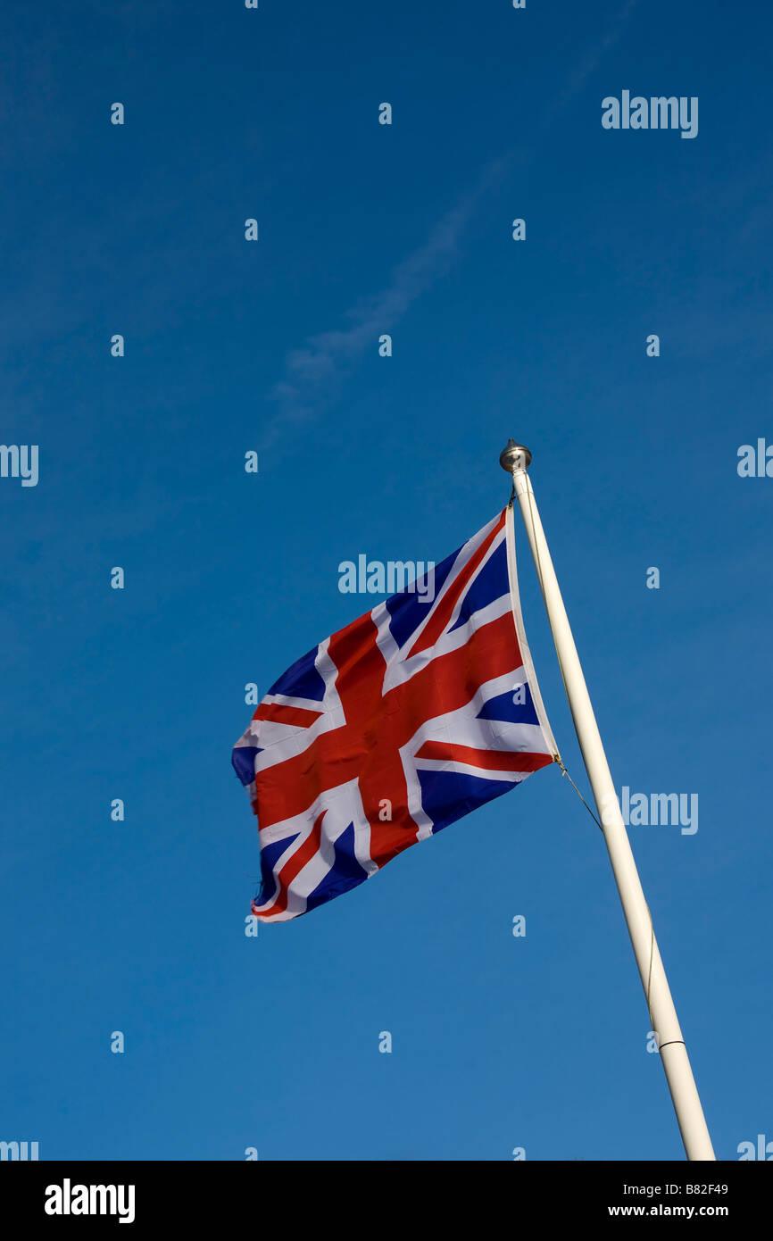 Union Jack flag flying on flagpole against blue sky - Stock Image