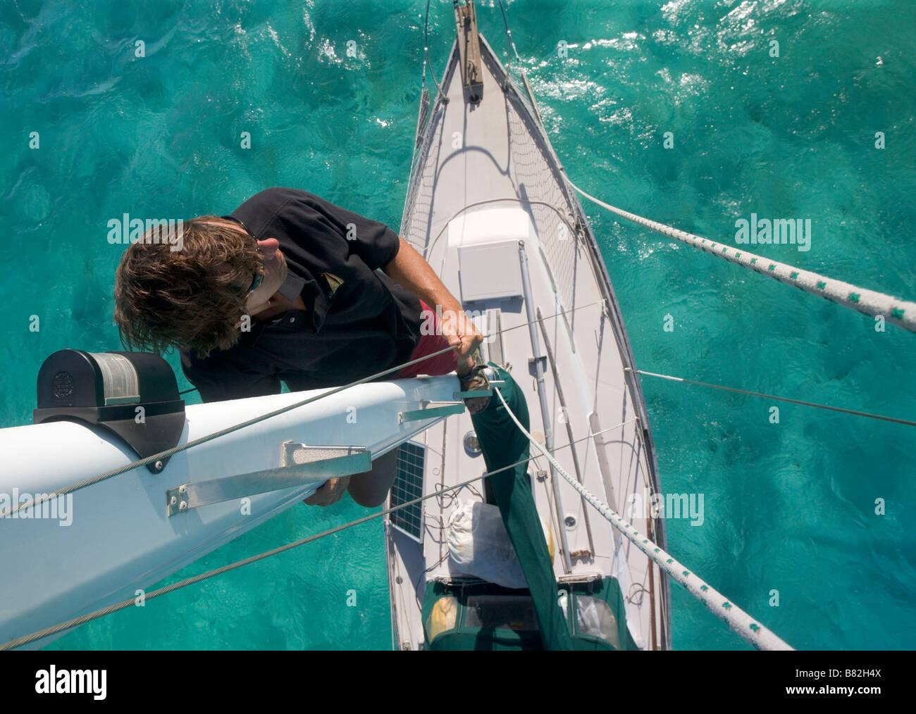 A sailor looks out from halfway up the mast on a cruising sailboat in the Caribbean - Stock Image