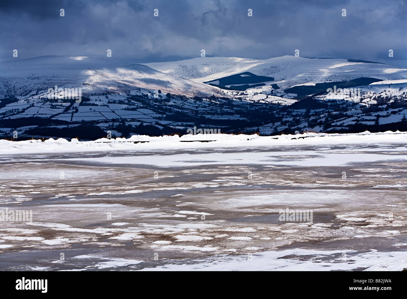 Keepers Pond frozen in winter with Black Mountains in distance Blorenge Wales UK - Stock Image