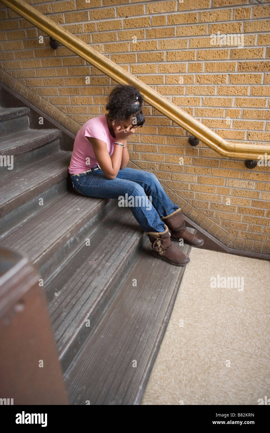teenage african american girl crying on staircase at school, sitting on step, vertical orientation - Stock Image