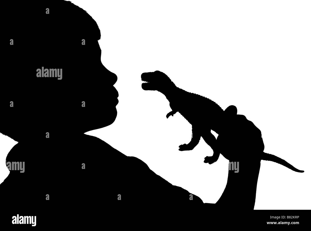 silhouette of boy looking at a dinosaur - Stock Image