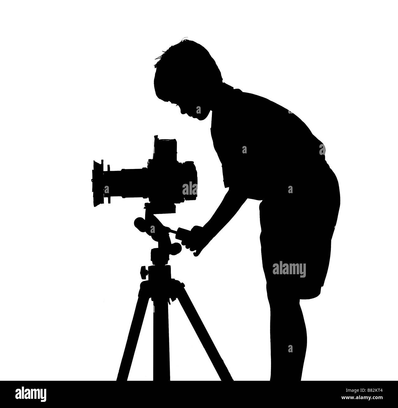 silhouette of boy taking a picture using a tripod and camera - Stock Image