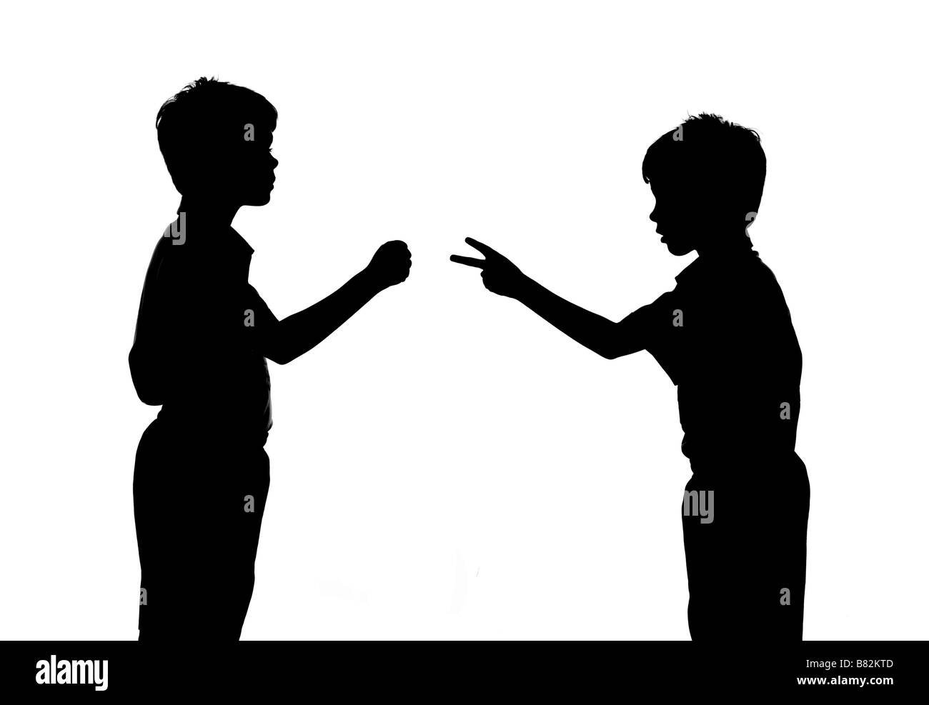 silhouette of two boys play rock scissors paper - Stock Image