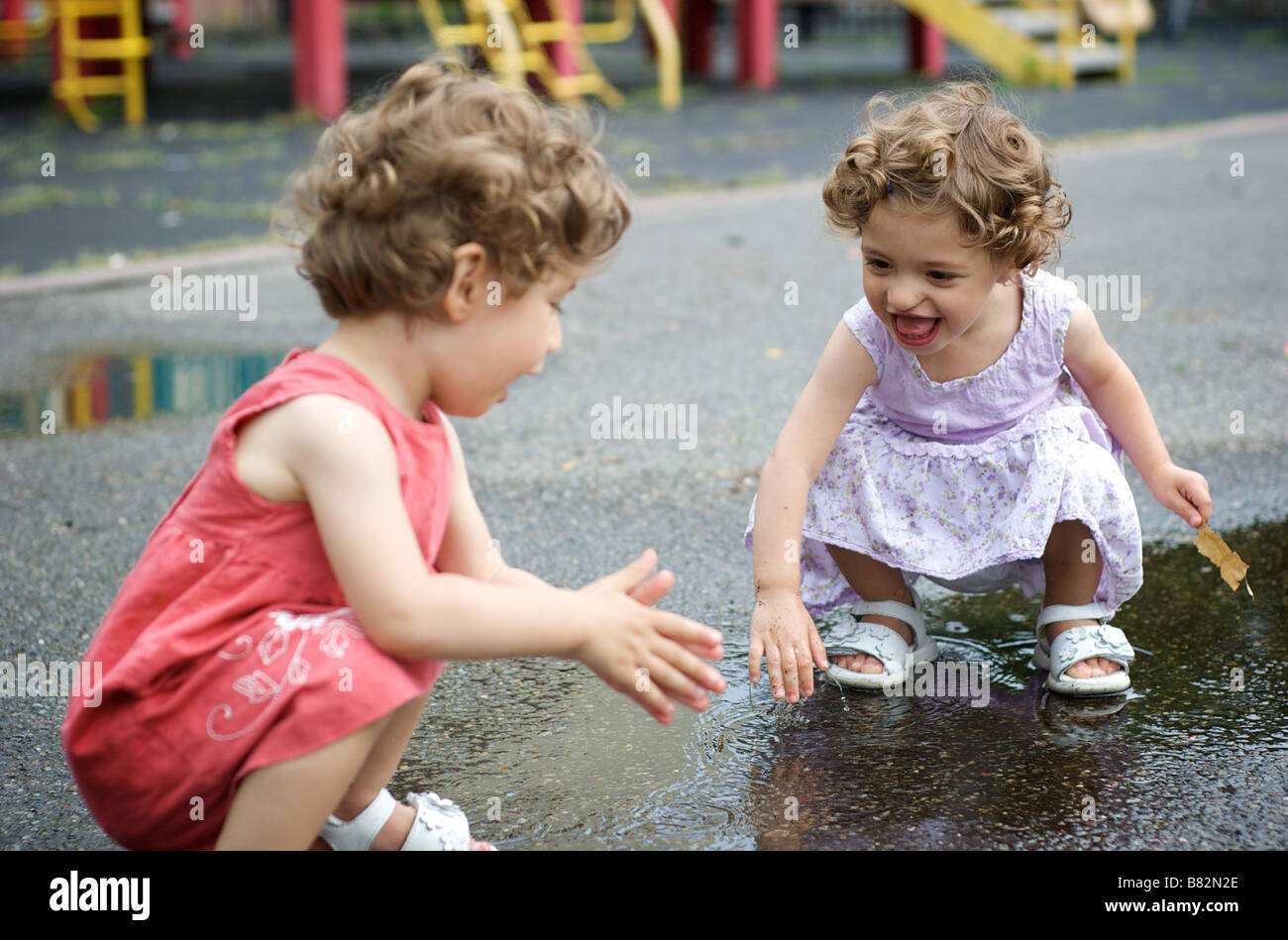 Two little girls playing in rain puddles at a playground in Brooklyn, New York, USA - Stock Image