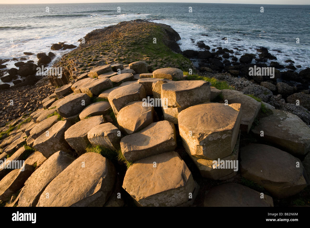 Causeway to Scotland. Hexagonal columns of basalt glow in the afternoon sun as they step down toward the crashing - Stock Image
