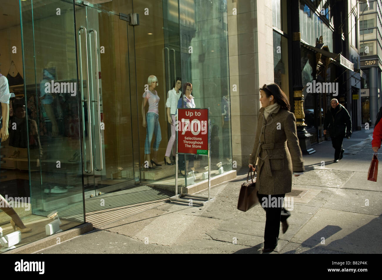 A pedestrian passes a Benetton store on Fifth Avenue in the midtown neighborhood of New York - Stock Image