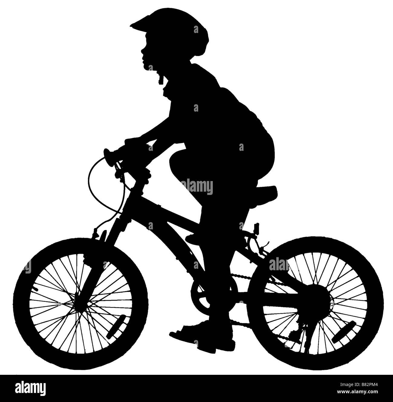 silhouette of boy riding a push bike - Stock Image