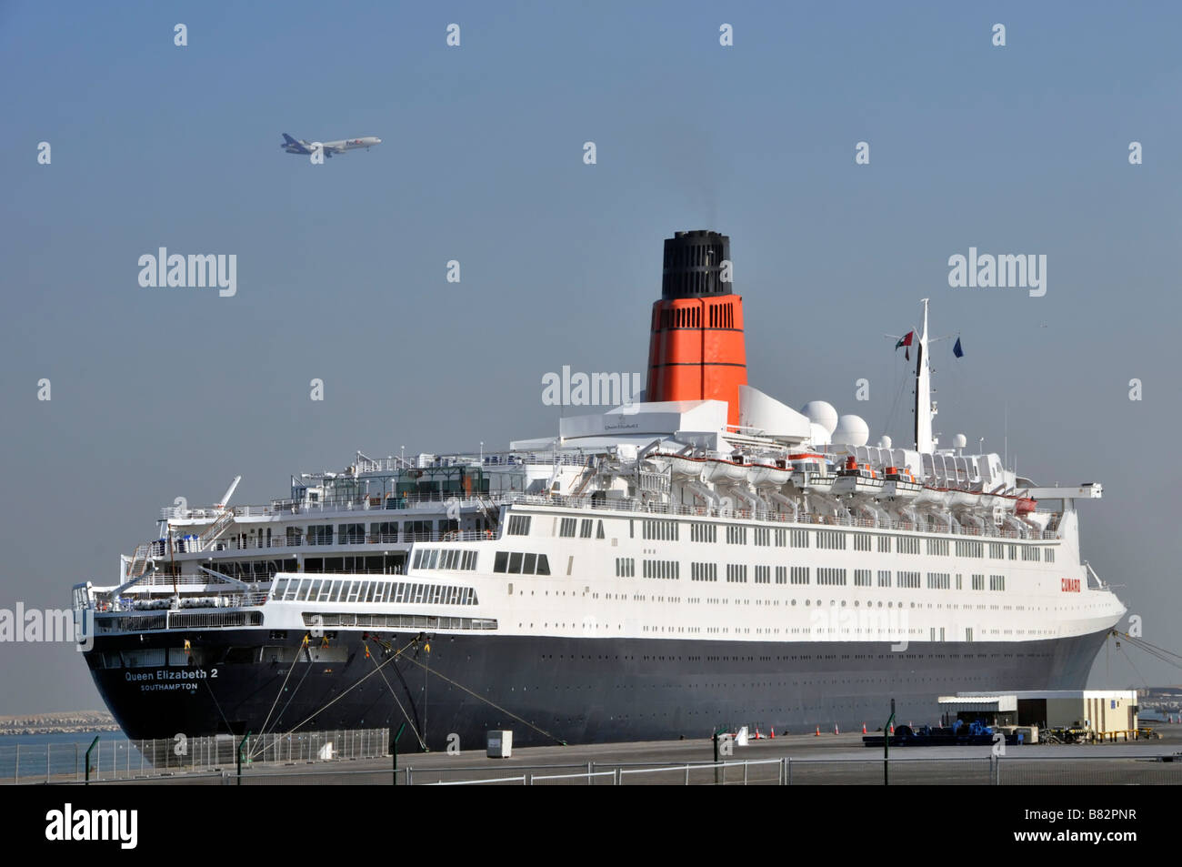 QE2 one time Cunard cruise liner moored at Port Rashid Dubai awaiting conversion to a floating hotel with aircraft - Stock Image