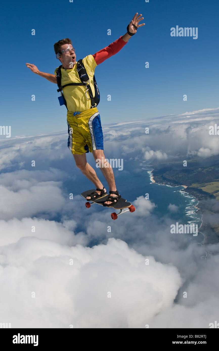 Skydiver is riding the big wave in the sky on his skate board over th North shore Oahu, Hawaii, America and having - Stock Image