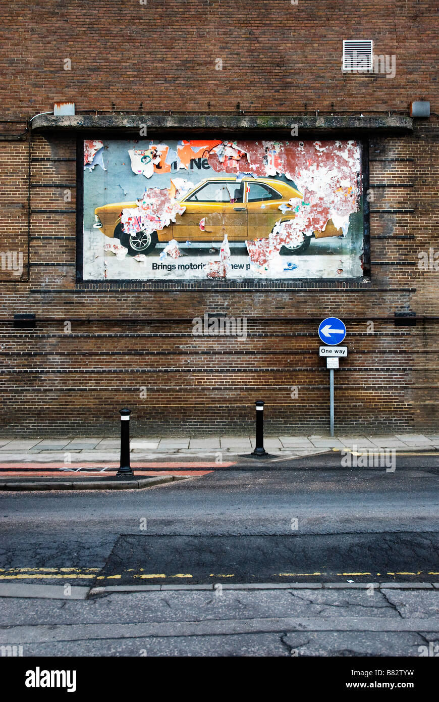 1970s Ford car poster on cinema brick wall, with one way sign - Stock Image