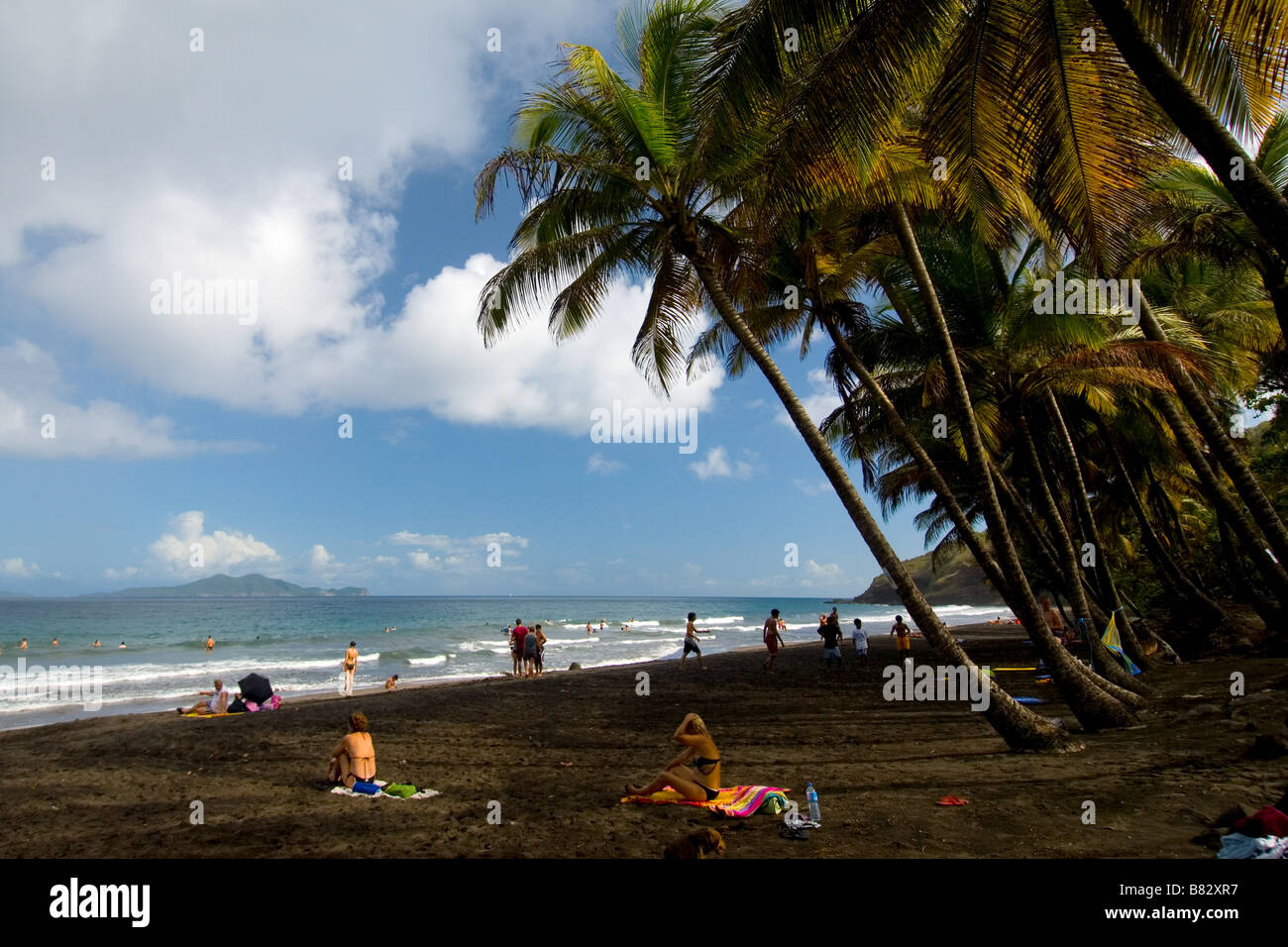 Nicaragua,  Black beach volcanic sand, palm trees, paradise, people at beach Stock Photo