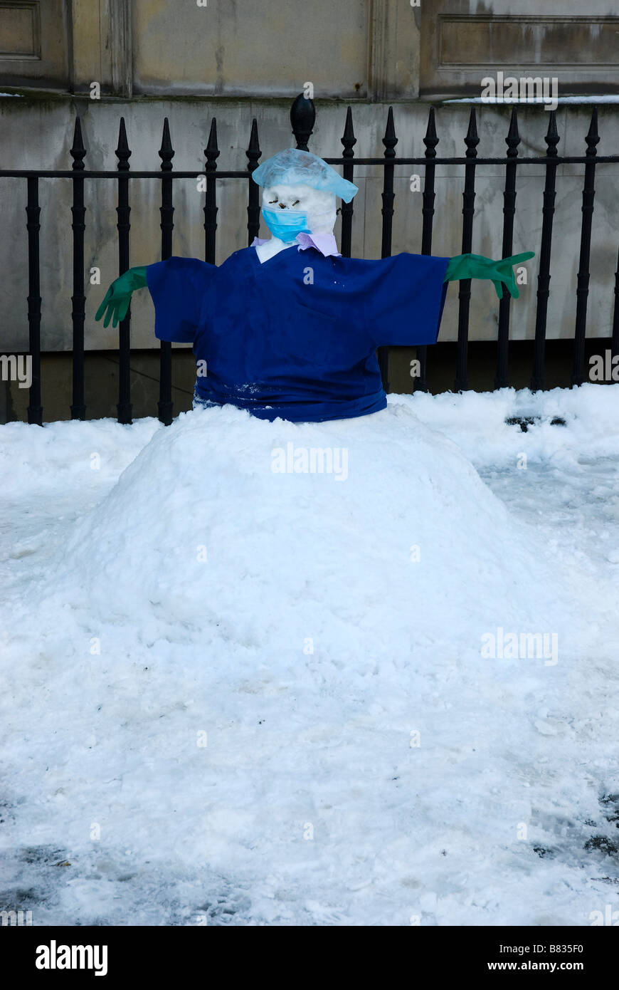 Snowman outside Royal College of Surgeons in London made using surgical clothing - Stock Image