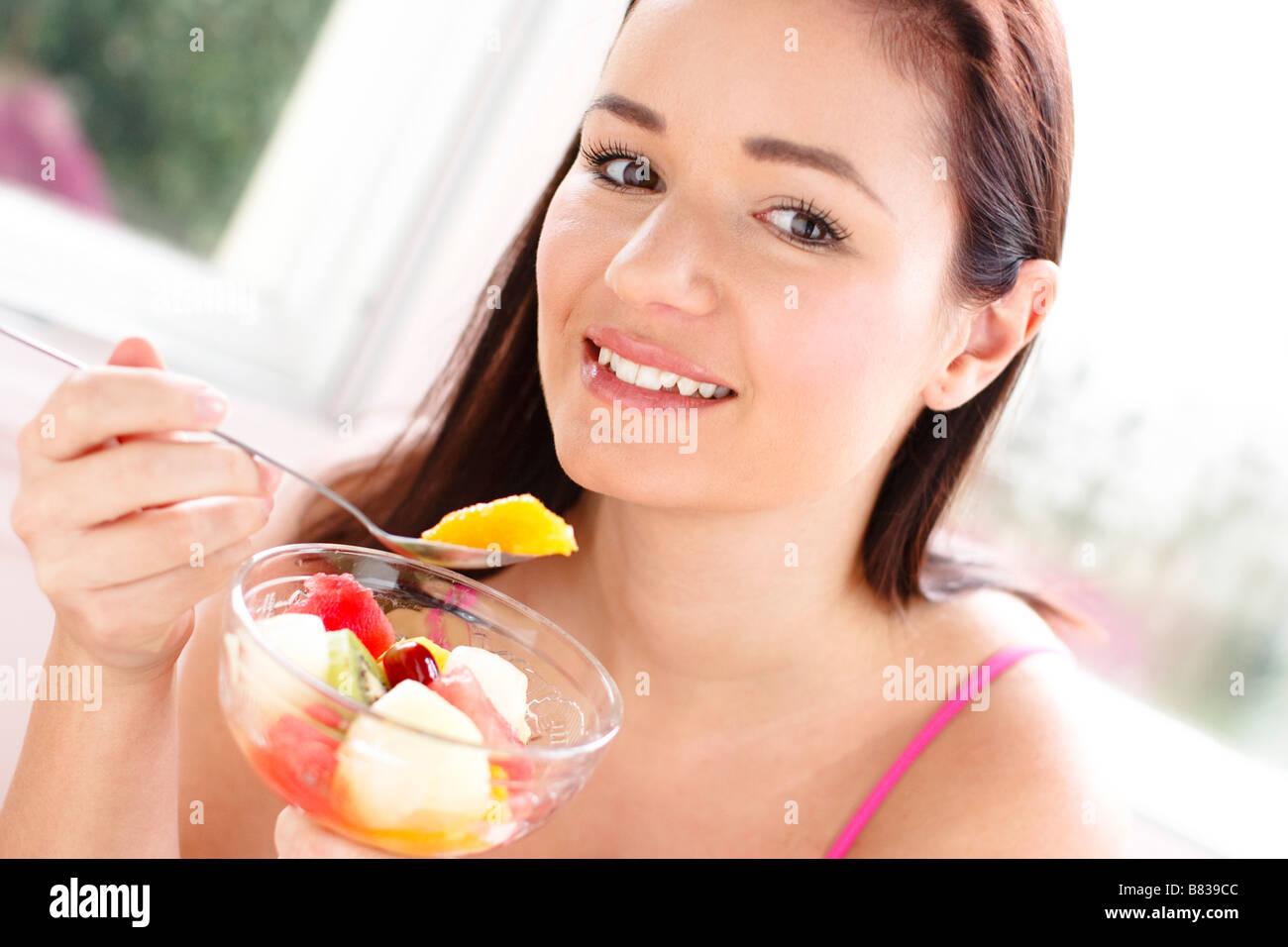 Girl eating fruit - Stock Image