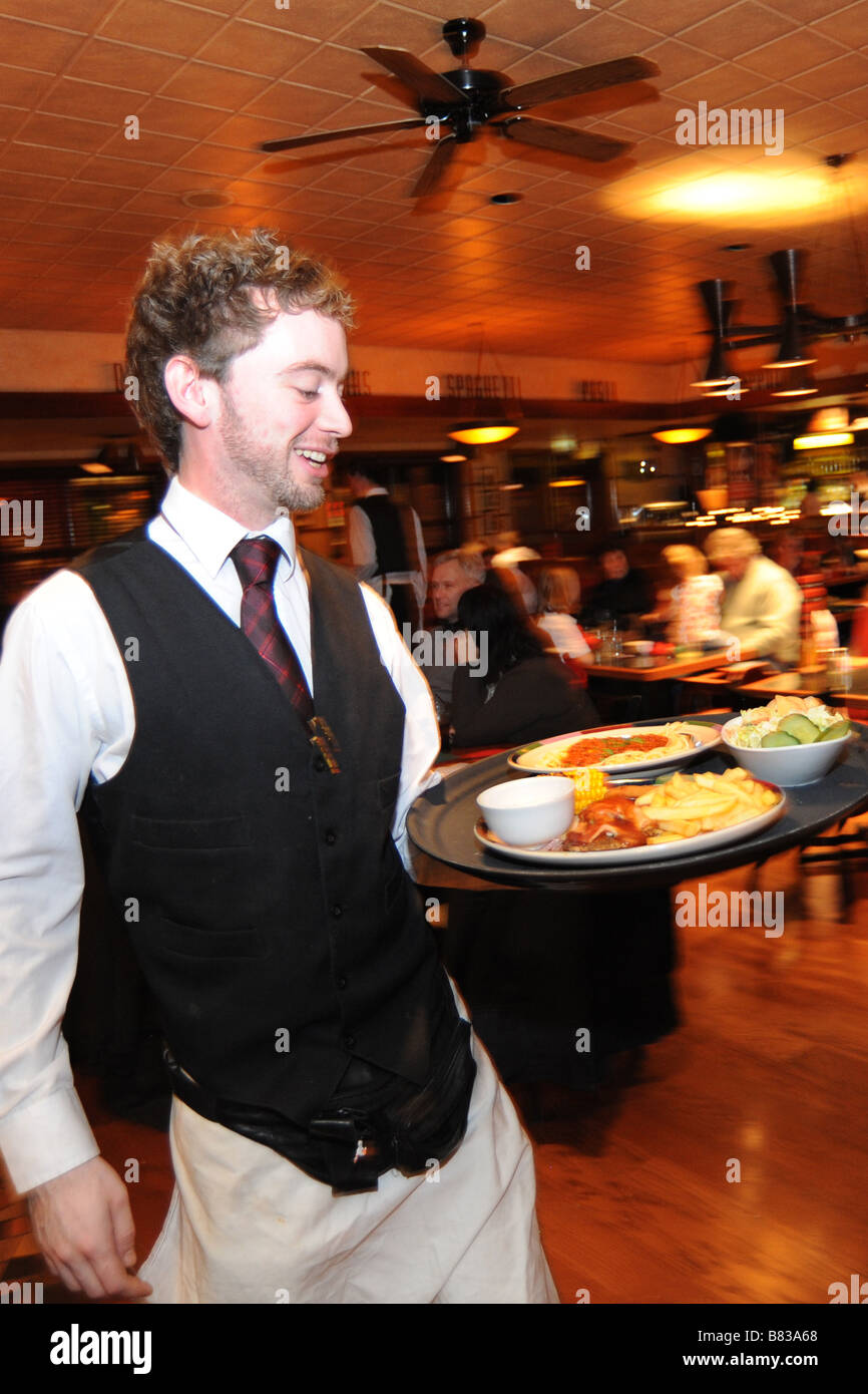 A waiter rushes with a tray of food in a busy restaurant Bradford West Yorkshire - Stock Image