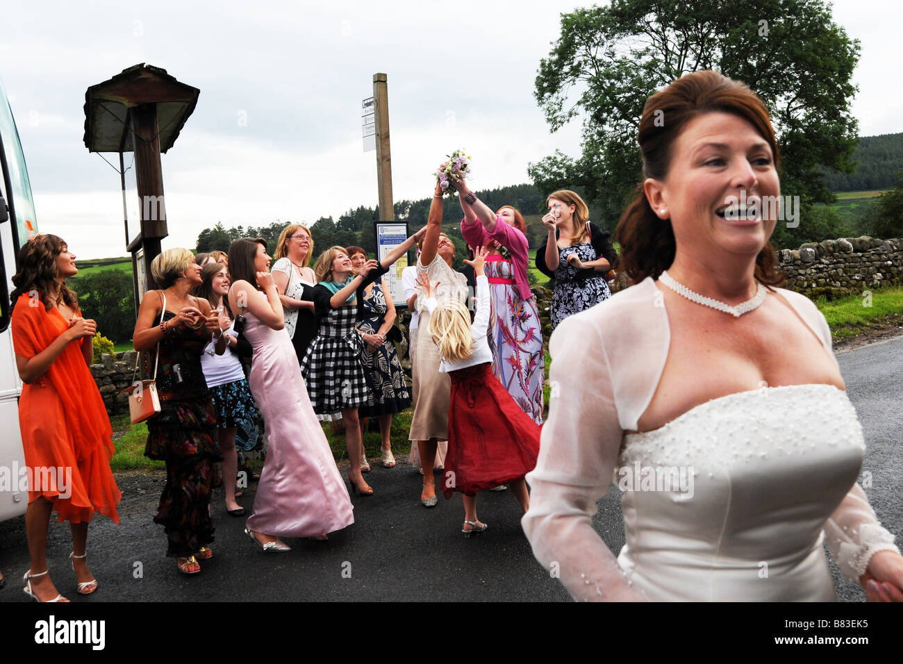 A bride throws her bouquet to wedding guests North Yorkshire - Stock Image