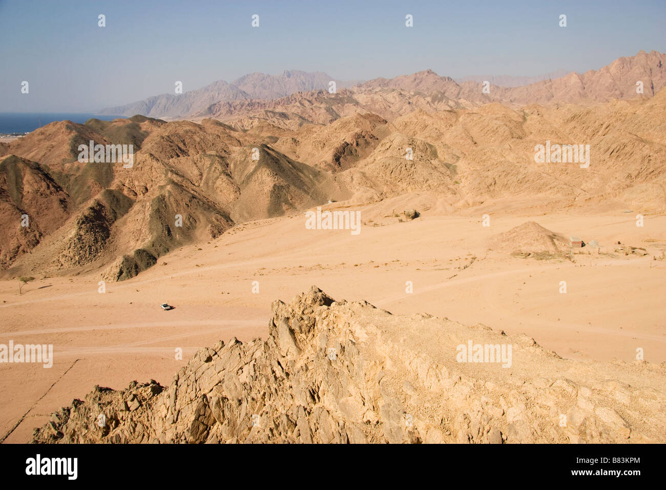 View South towards Laguna Bay from a hill in the desert above the Sinai resort of Dahab in Egypt - Stock Image