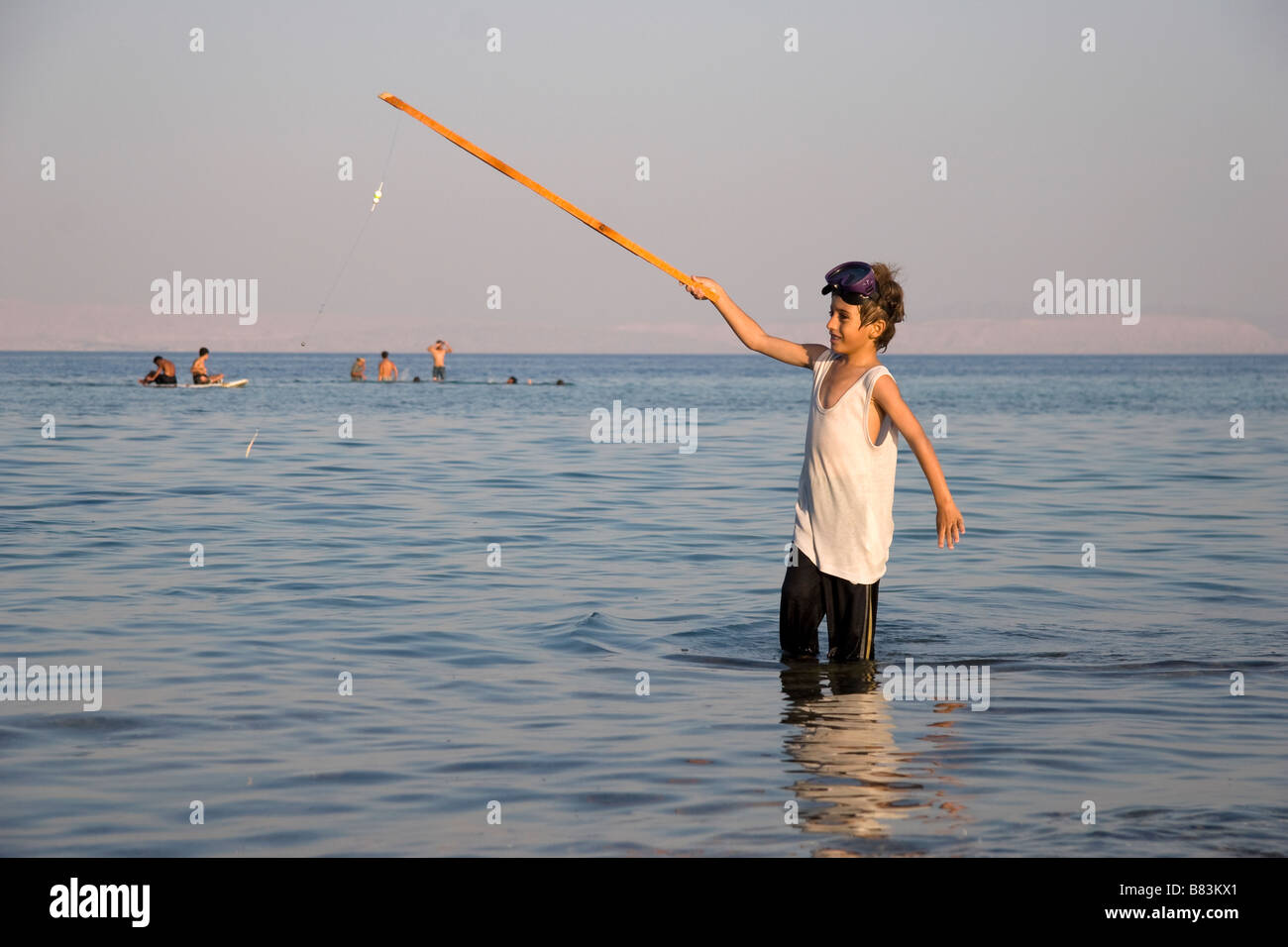 Local Bedouin boy fishing off the beach in Asilah Bay in the Sinai resort of Dahab in Egypt - Stock Image