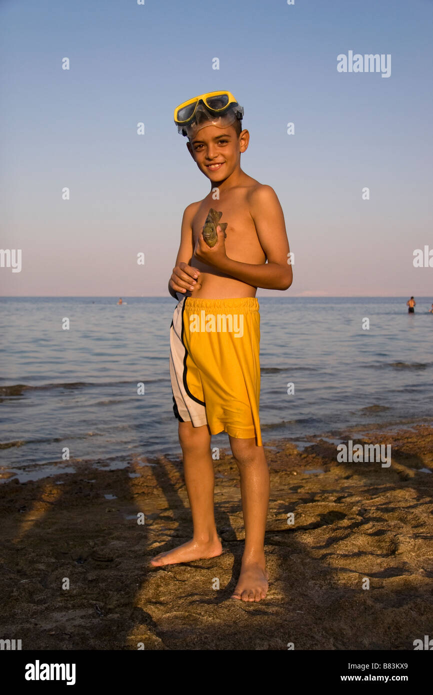 Local Bedouin boy shows a fish he caught snorkeling in Asilah Bay in the Sinai resort of Dahab in Egypt - Stock Image