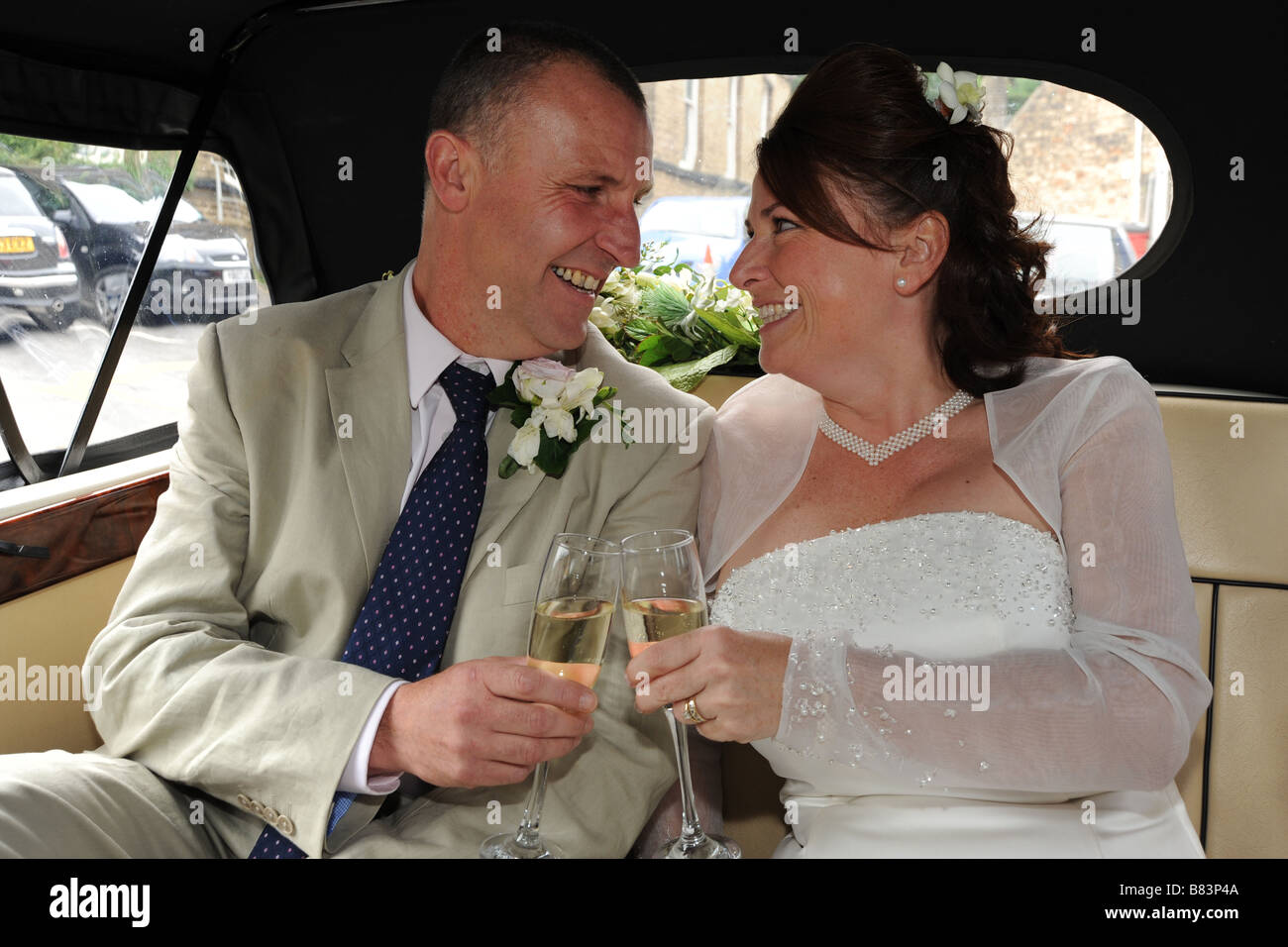 Newly wed couple  toasting with champagne in their car,North Yorkshire Model Released - Stock Image