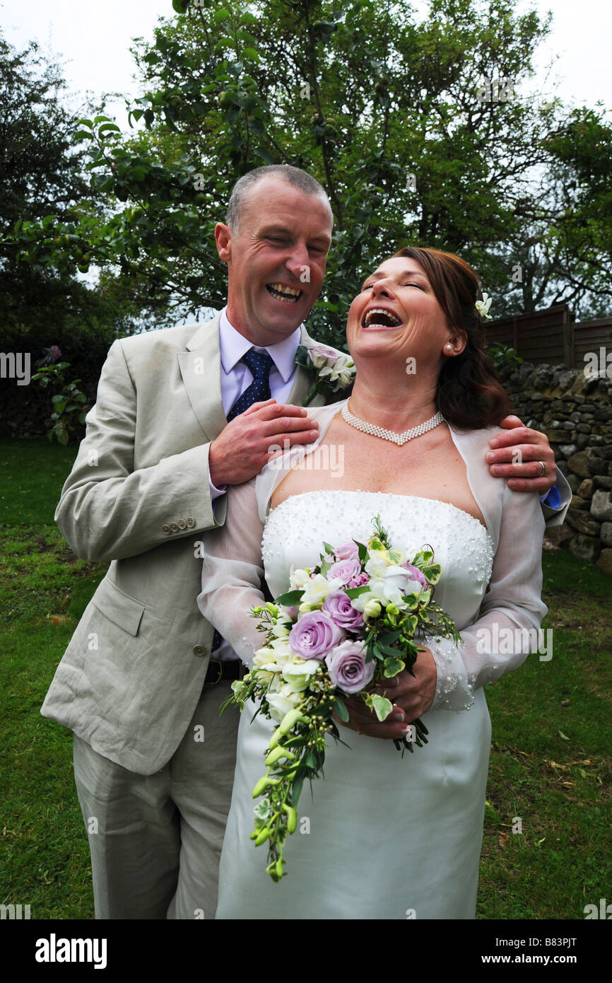Newly wed couple laughing on their wedding day, Model Released - Stock Image