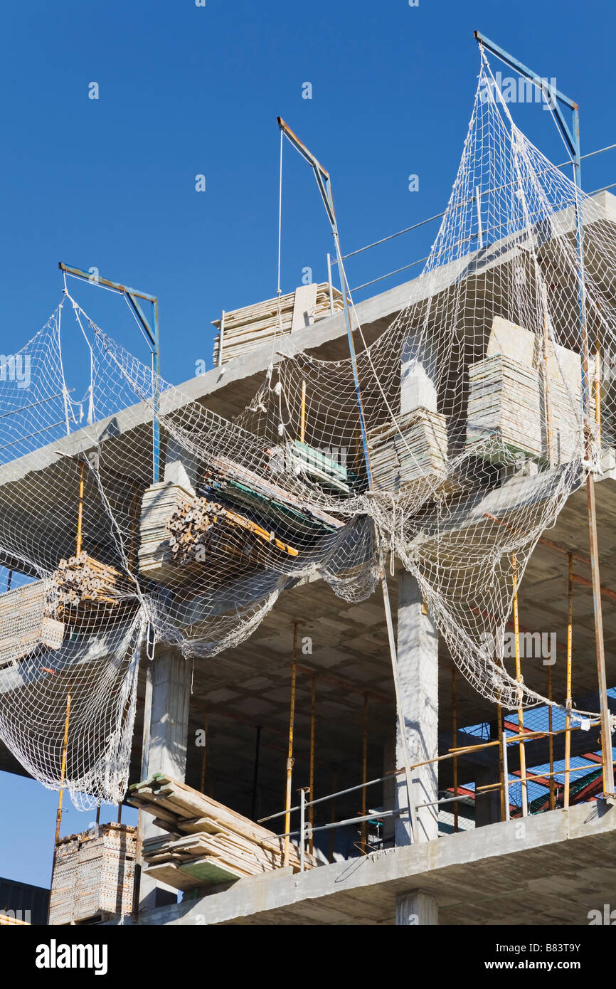 Building under construction with safety netting against falling debris - Stock Image