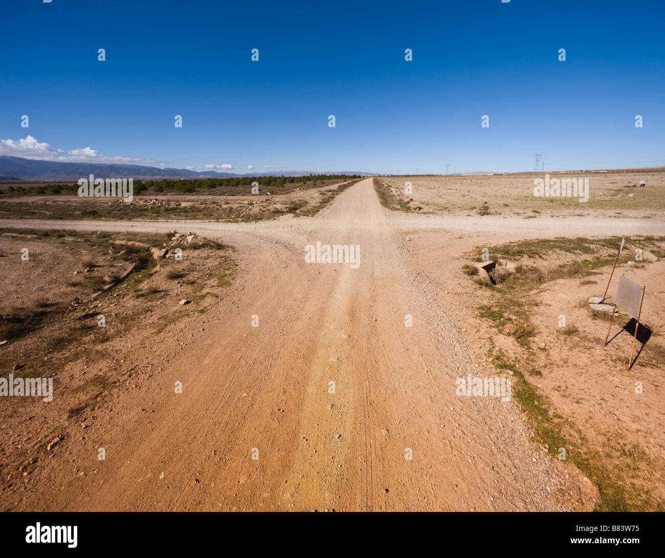 A choice of direction at crossroads in barren countryside near La Calahorra Granada Province Spain - Stock Image
