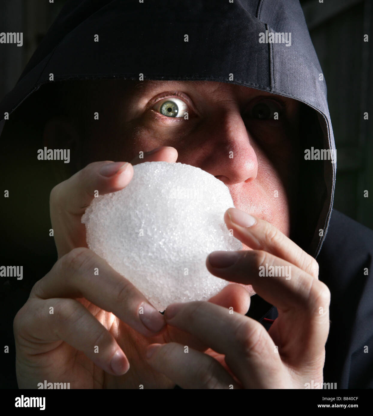 A man holds a snowball as he plans to throw it at his victim - Stock Image