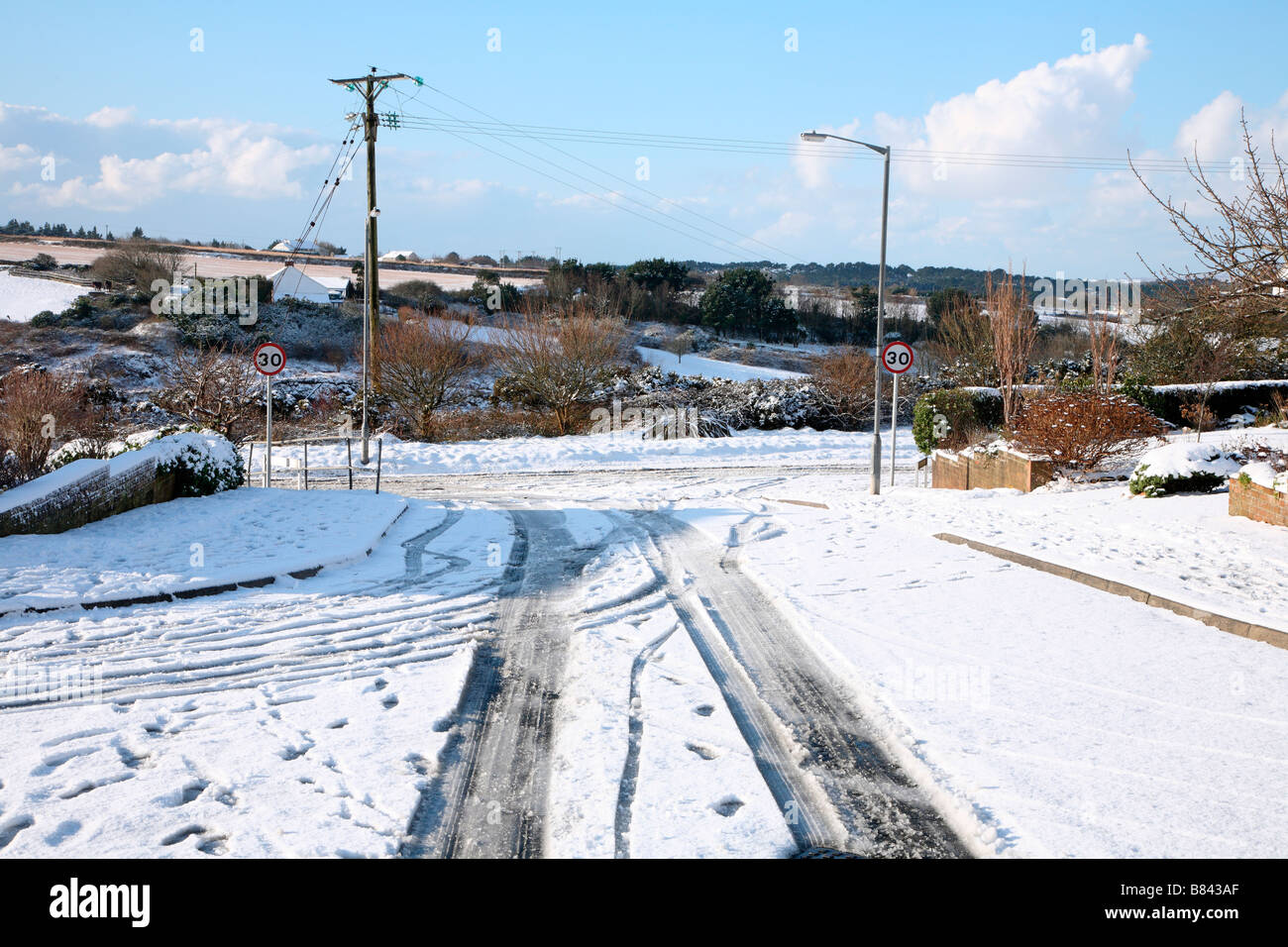 Snow and ice on a road in a housing estate in Cornwall UK. - Stock Image