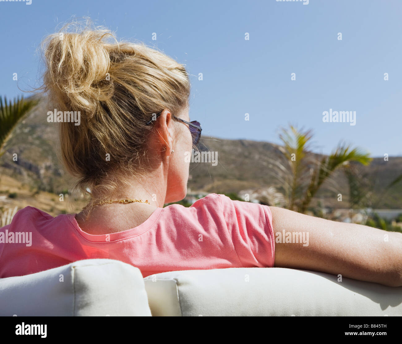 Middle aged lady relaxing in luxurious surroundings - Stock Image