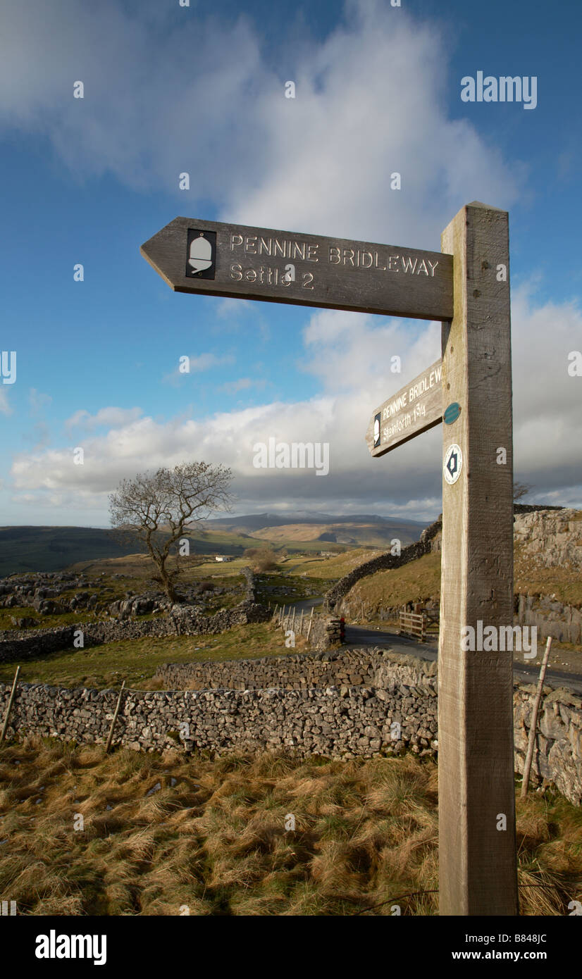 pennine bridleway signpost at winskill in the yorkshire dales with dry stone walls and snow covered ingleborough - Stock Image
