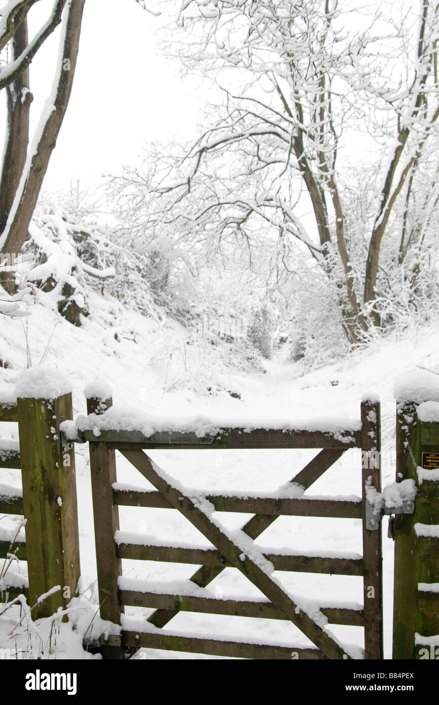Closed wooden gate on footpath covered in fresh snow - Stock Image