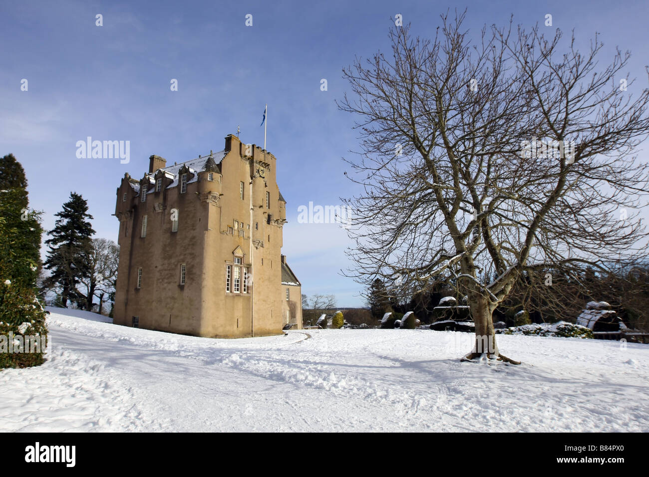 Exterior view of Crathes Castle and grounds near Banchory, Aberdeenshire, Scotland, UK covered in snow during winter - Stock Image