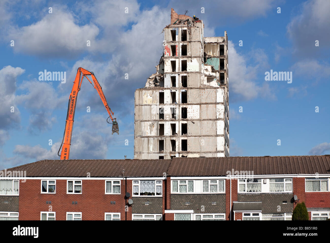 A residential tower block being demolished behind a row of houses in Birmingham England UK - Stock Image