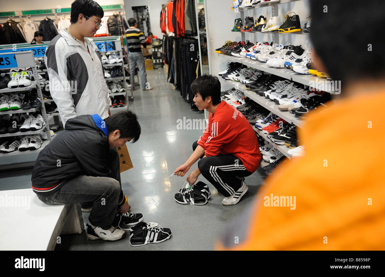 Chinese young men trying on Adidas shoes in a store in Beijing China 11-Feb-2009 - Stock Image