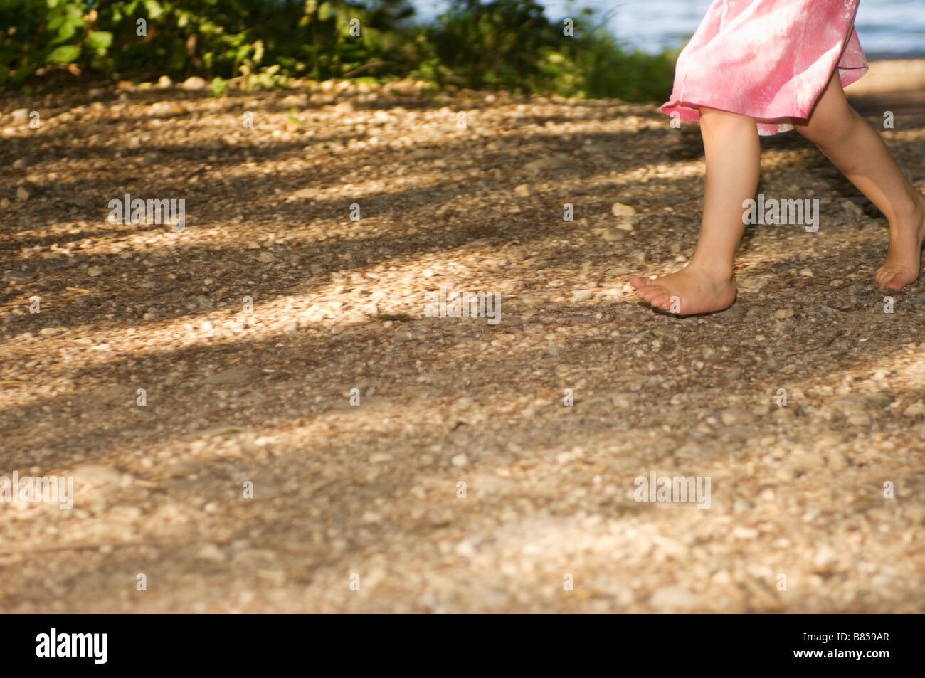 detail of little girl walking barefoot through forest - Stock Image