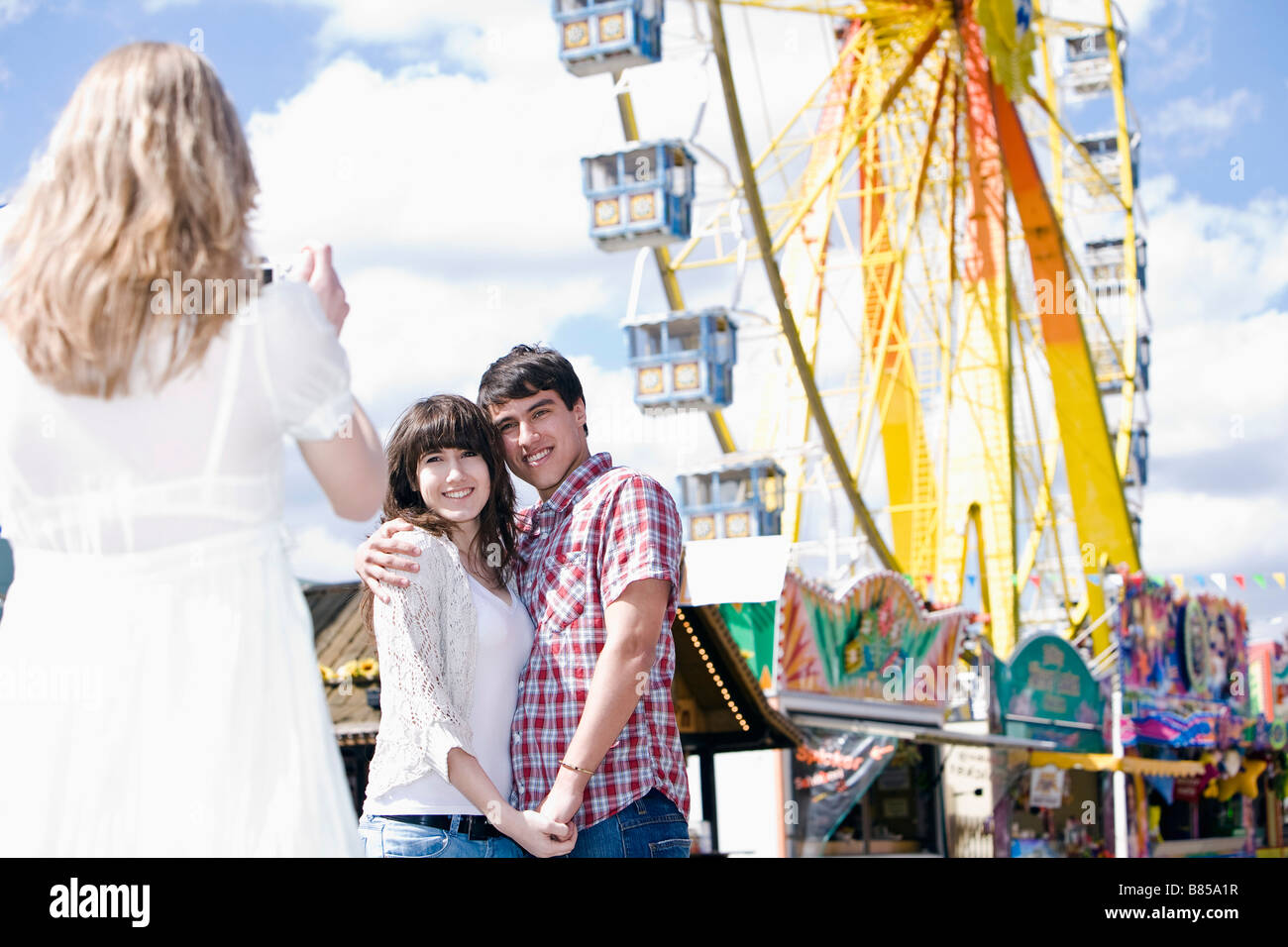 girl taking picture of teenage couple - Stock Image