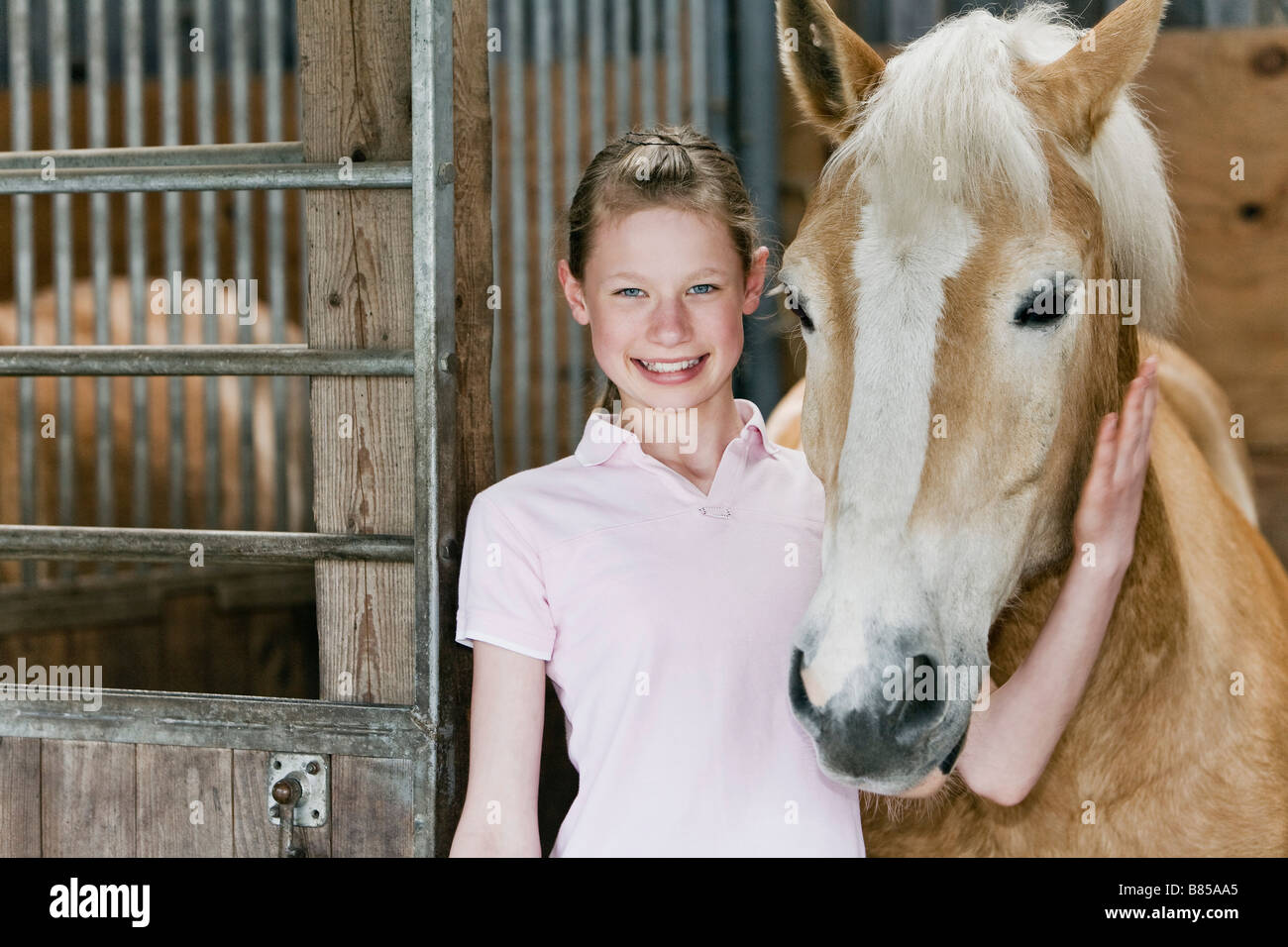 portrait of young girl with horse in stable - Stock Image