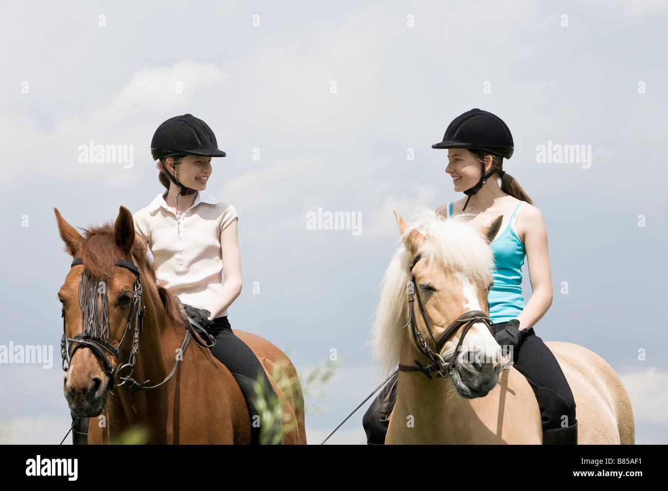 two girls doing horseback riding - Stock Image