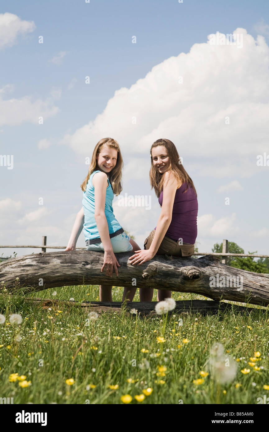 portrait of two girls sitting on tree trunk at horse ranch - Stock Image