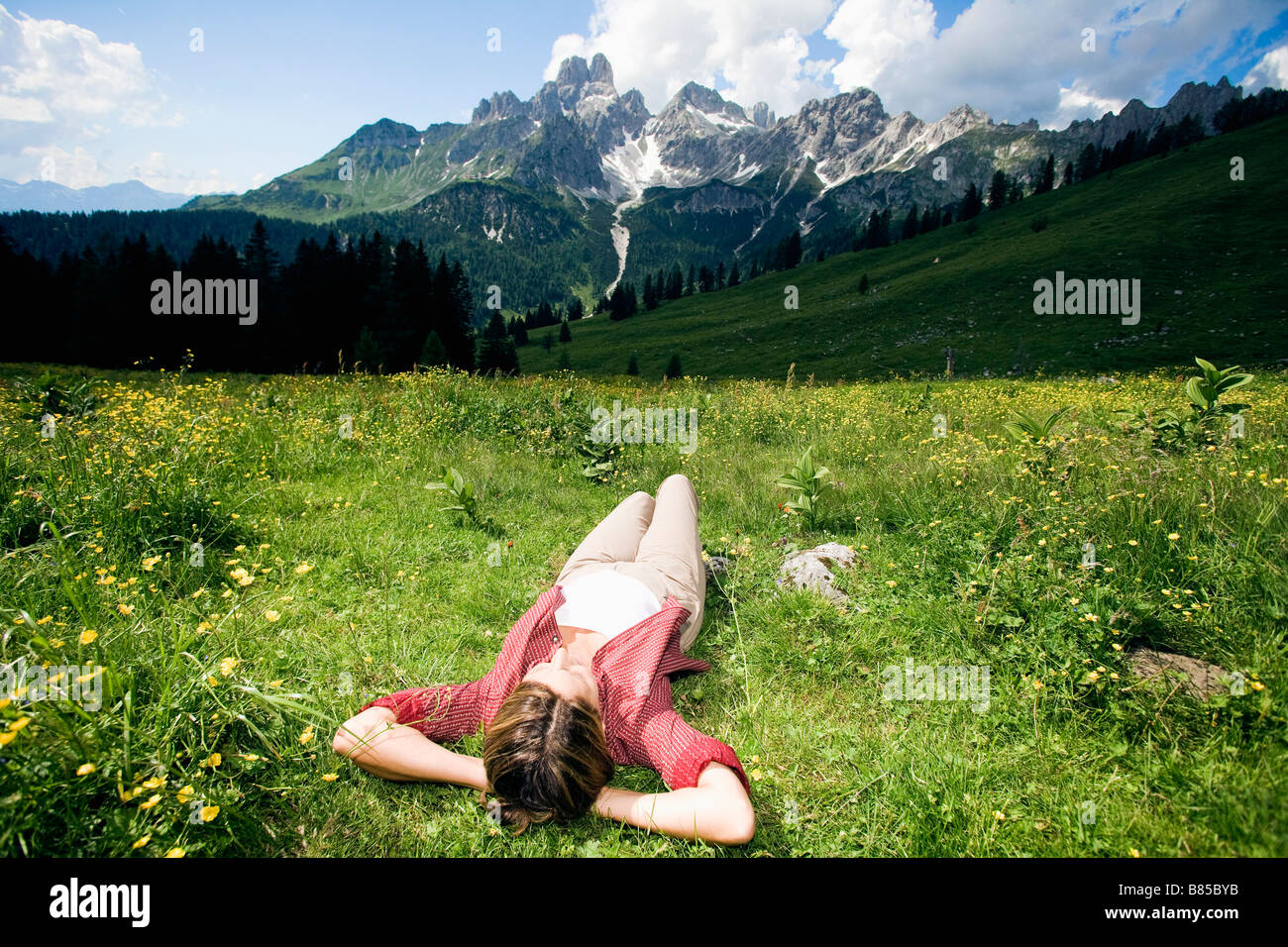 mature woman lying in grass in the mountains relaxing - Stock Image