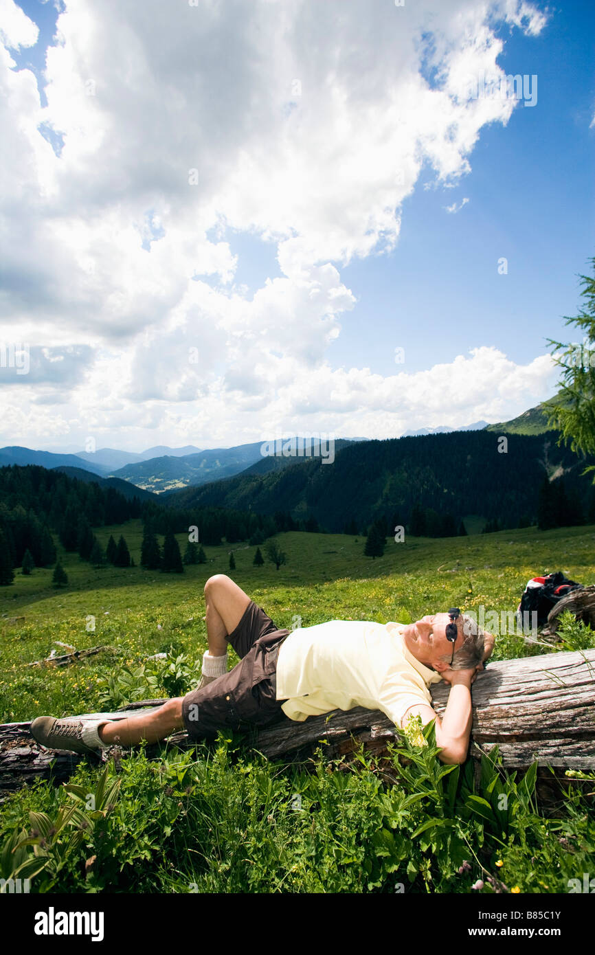 mature man dozing on log in the mountains - Stock Image