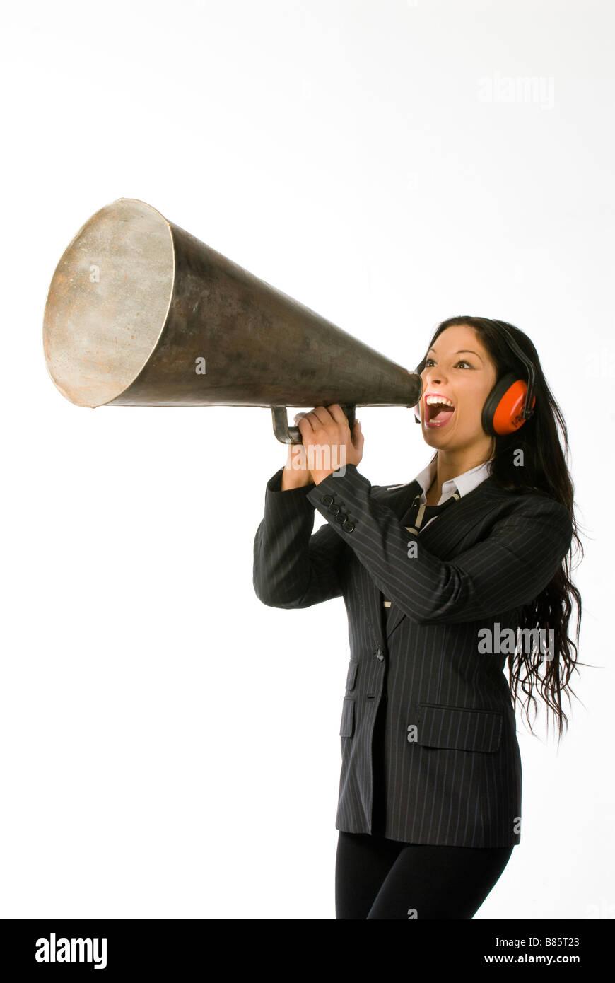 businesswoman wearing ear defenders shouting down loud hailer - Stock Image