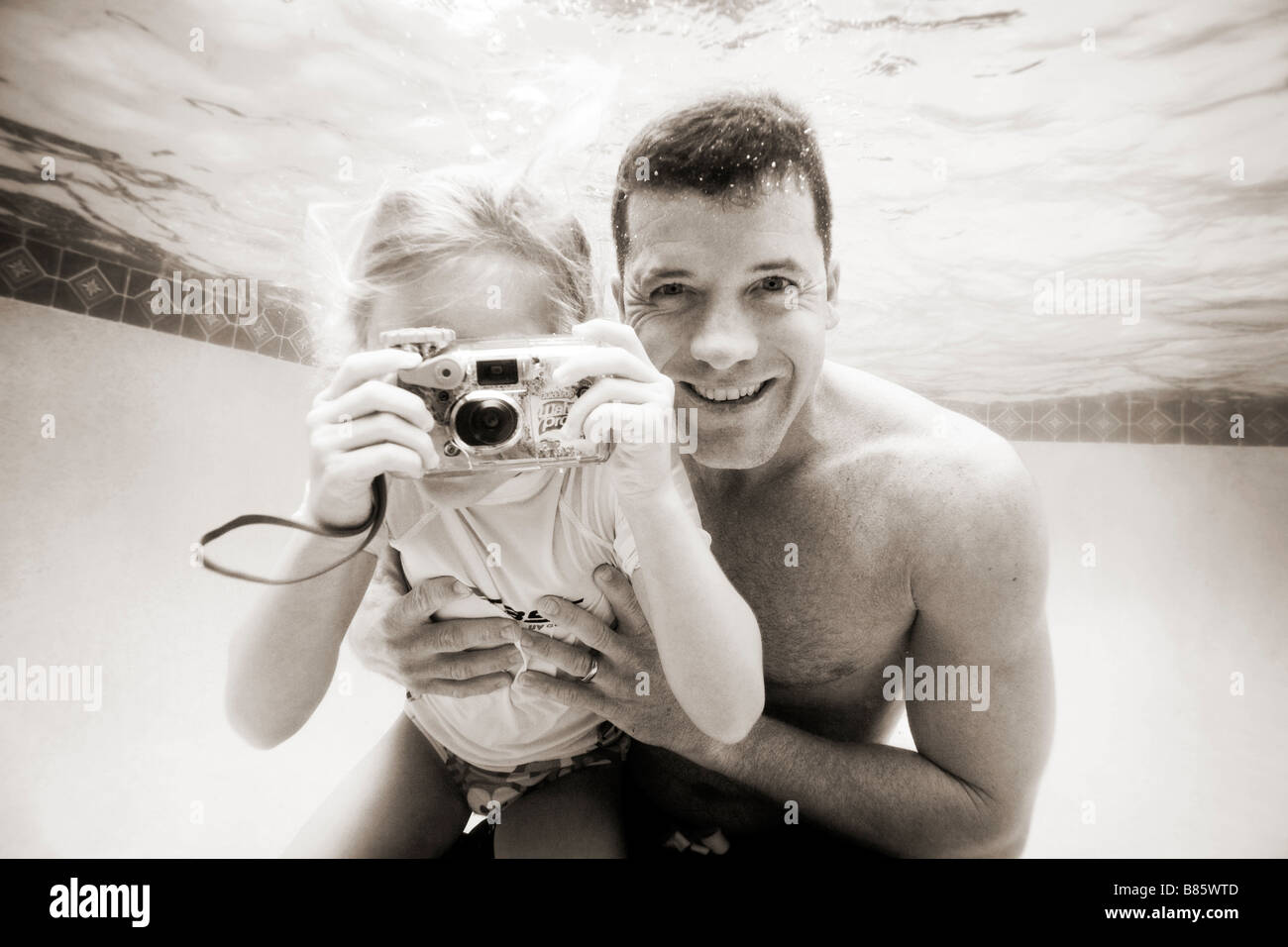 family in swimming pool - Stock Image