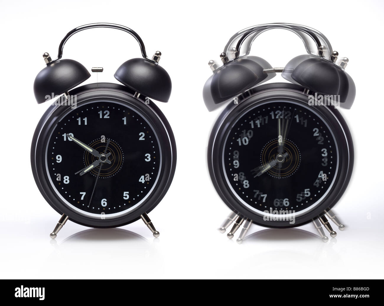 Two alarm clocks one still one ringing on white - Stock Image